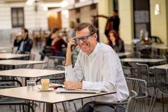 Uśmiechnięty atrakcyjny elegancki dorośleć mężczyzna używa mądrze telefon sprawdza online obsiadanie na zewnątrz sklep z kawą zdjęcie royalty free