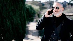 Uśmiechnięty atrakcyjny mężczyzna jest ubranym czarną kurtkę i opowiada przy smartphone podczas gdy wydający czas w miasto parku  Fotografia Royalty Free
