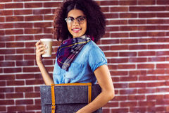 Uśmiechnięty atrakcyjny modniś z odczuwaną torbą i kawą fotografia stock
