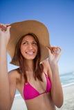 Uśmiechnięty atrakcyjny nastolatek trzyma jej kapeluszowego rondo przed Fotografia Stock