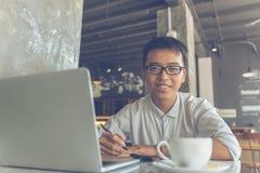 Uśmiechnięty Azjatycki freelancer pisze notatkach przy kawiarnią zdjęcie stock