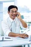 Uśmiechnięty azjatykci biznesmen dzwoni someone Zdjęcia Royalty Free