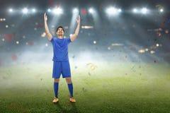 Uśmiechnięty azjatykci futbolista po wygrywać dopasowanie obraz stock