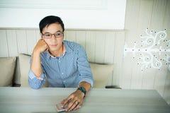 Uśmiechnięty azjatykci mężczyzna w przypadkowym ubierającym działaniu z biura podczas gdy fotografia stock