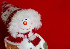 Uśmiechnięty bałwanu posążek na czerwonym tle jako zima wakacji pojęcie Obraz Stock