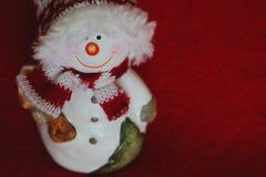 Uśmiechnięty bałwanu posążek na czerwonym tle jako zima wakacji pojęcie Zdjęcia Royalty Free