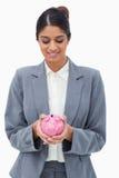 Uśmiechnięty banka pracownik patrzeje prosiątko banka w ona ręki Fotografia Stock