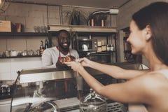 Uśmiechnięty barista mężczyzna daje dziewczynie jej rozkazowi obrazy stock