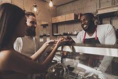 Uśmiechnięty barista mężczyzna daje dziewczynie jej rozkazowi zdjęcia stock