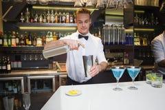 Uśmiechnięty barman przygotowywa napój przy baru kontuarem Zdjęcia Royalty Free