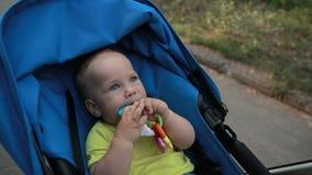 Uśmiechnięty berbeć chłopiec obsiadanie w pram outdoors zbiory