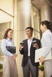Uśmiechnięty biznesmen daje kawie dwa potomstw bizneswoman przy biurem Fotografia Royalty Free