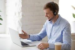 Uśmiechnięty biznesmen patrzeje laptopu ekran w hełmofonach fotografia royalty free