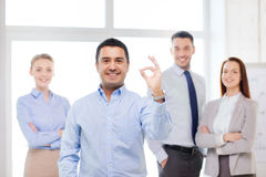 Uśmiechnięty biznesmen pokazuje znaka w biurze Obraz Royalty Free