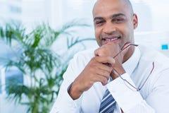 Uśmiechnięty biznesmen trzyma czytelniczych szkła Obraz Royalty Free