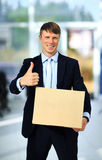 Uśmiechnięty biznesmen trzyma karton Zdjęcia Stock