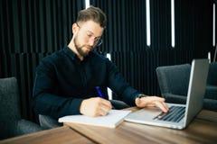 Uśmiechnięty biznesmen z laptopem i pisze zawiadomieniu w dokumentach przy biurem obraz royalty free
