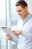 Uśmiechnięty biznesmen z pastylka komputerem osobistym w biurze obrazy stock