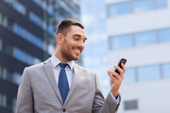 Uśmiechnięty biznesmen z smartphone outdoors Zdjęcie Royalty Free