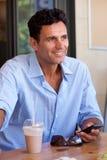 Uśmiechnięty biznesmena obsiadanie z telefonem komórkowym obrazy royalty free