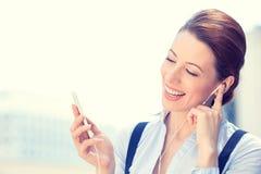 Uśmiechnięty biznesowej kobiety odprowadzenie na ulicznym słuchaniu muzyka na telefonie komórkowym fotografia royalty free