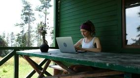 Uśmiechnięty biznesowej kobiety turystyczny freelancer pisać na maszynie na laptopie outdoors w lecie przeciw zielonej ścianie pr zbiory wideo