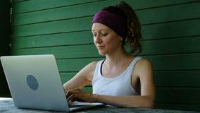 Uśmiechnięty biznesowej kobiety turystyczny freelancer pisać na maszynie na laptopie outdoors w lecie przeciw zielonej ścianie zbiory