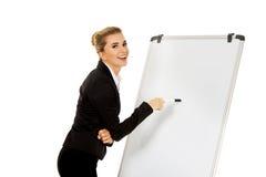 Uśmiechnięty biznesowej kobiety writing na flipchart Zdjęcia Stock