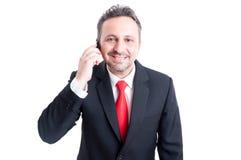 Uśmiechnięty biznesowy mężczyzna opowiada na smartphone Zdjęcie Royalty Free