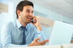 Uśmiechnięty biznesowy mężczyzna opowiada na telefonie komórkowym w biurze Obrazy Stock