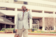 Uśmiechnięty biznesowy mężczyzna opowiada na telefonu komórkowego mienia teczki odprowadzenia puszku ulicę Obrazy Stock