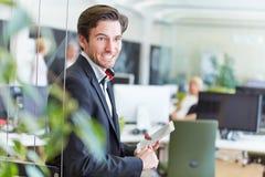 Uśmiechnięty biznesowy mężczyzna z pastylka pecetem w biurze Zdjęcia Royalty Free