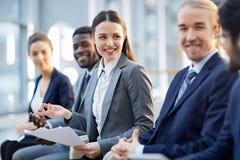 Uśmiechnięty Biznesowy widowni obsiadanie w rzędzie obraz stock
