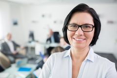 Uśmiechnięty bizneswoman Jest ubranym Eyeglasses W biurze zdjęcia royalty free