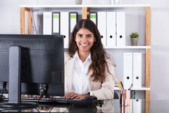 Uśmiechnięty bizneswoman pisać na maszynie na klawiaturze zdjęcie royalty free