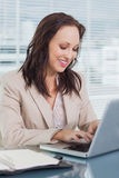 Uśmiechnięty bizneswoman pisać na maszynie na jej laptopie Zdjęcie Royalty Free