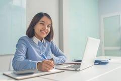 Uśmiechnięty bizneswoman pisze notatce w biznesowym pokoju zdjęcia stock
