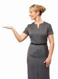 Uśmiechnięty bizneswoman Pokazuje Niewidzialnego produkt Zdjęcia Stock