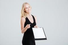 Uśmiechnięty bizneswoman pokazuje pustego schowek i wskazuje przy kamerą Zdjęcia Stock