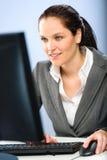 Uśmiechnięty bizneswoman pracuje na jej komputerze Obraz Royalty Free
