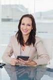 Uśmiechnięty bizneswoman pracuje na jej pastylka komputerze osobistym Fotografia Royalty Free