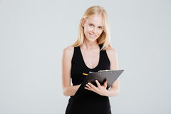 Uśmiechnięty bizneswoman robi notatkom w schowku odizolowywającym Obraz Stock