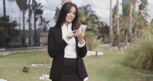 Uśmiechnięty bizneswoman sprawdza jej telefon komórkowego zdjęcie wideo