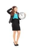 Uśmiechnięty bizneswoman trzyma ściennego zegar Fotografia Royalty Free