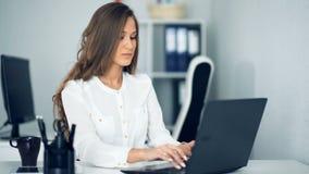 Uśmiechnięty bizneswoman używa jej laptop w biurze zbiory