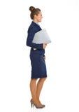 Uśmiechnięty bizneswoman w kostium pozyci w profilowej mienie kartotece zdjęcia royalty free
