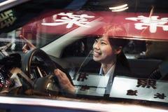 Uśmiechnięty bizneswoman wskazuje z samochodu podczas gdy jadący przez Pekin przy nocą Fotografia Stock