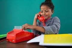 Uśmiechnięty bizneswoman wybiera numer liczby na ziemi linii telefonie Zdjęcia Royalty Free