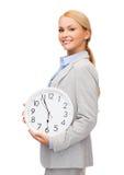 Uśmiechnięty bizneswoman z ściennym zegarem zdjęcie royalty free