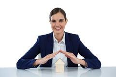 Uśmiechnięty bizneswomanu chronienia domu model z rękami Obraz Stock